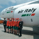 The bright red of the cabincrew's uniforms makes a vivid splash of colour as they pose in front of a Boeing 757.